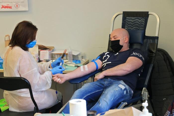 Mężczyzna oddający krew. Obok, po lewej, pielęgniarka