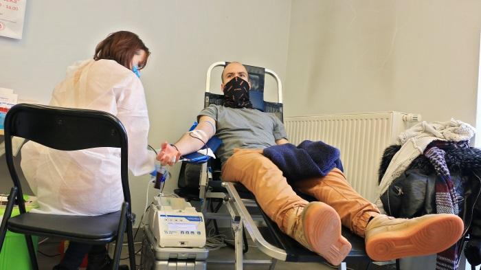 Mężczyzna w żółtych spodniach. Siedzi na specjalnym krześle-leżaku i oddaje krew. Obok czuwa pielęgniarka