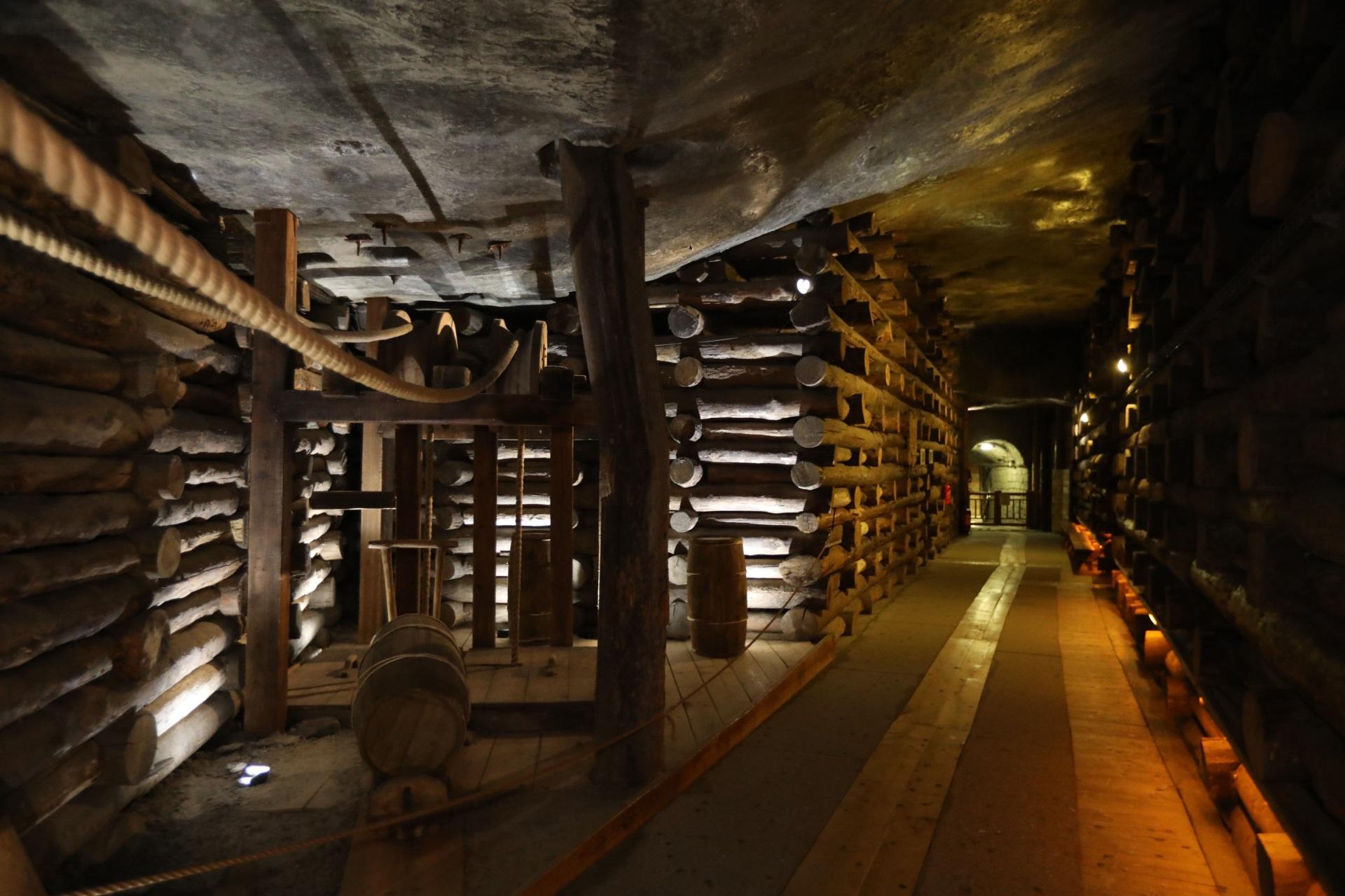 Komora Urszula na Trasie Turystycznej. Po lewej stronie kadru drewniany krzyż ręczny, w głębi wyłożona drewnem droga do komory Michałowice
