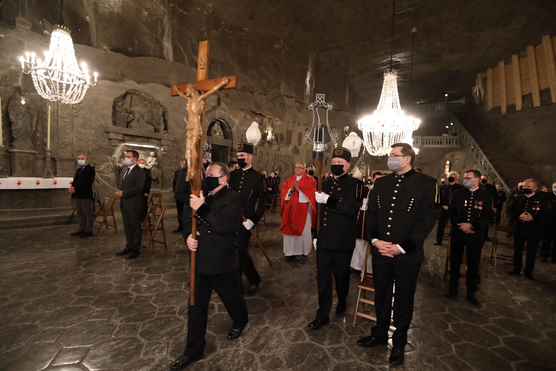 Początek barbórkowej mszy. Przed arcybiskupem Jędraszewskim idzie górnik z drewnianym krzyżem
