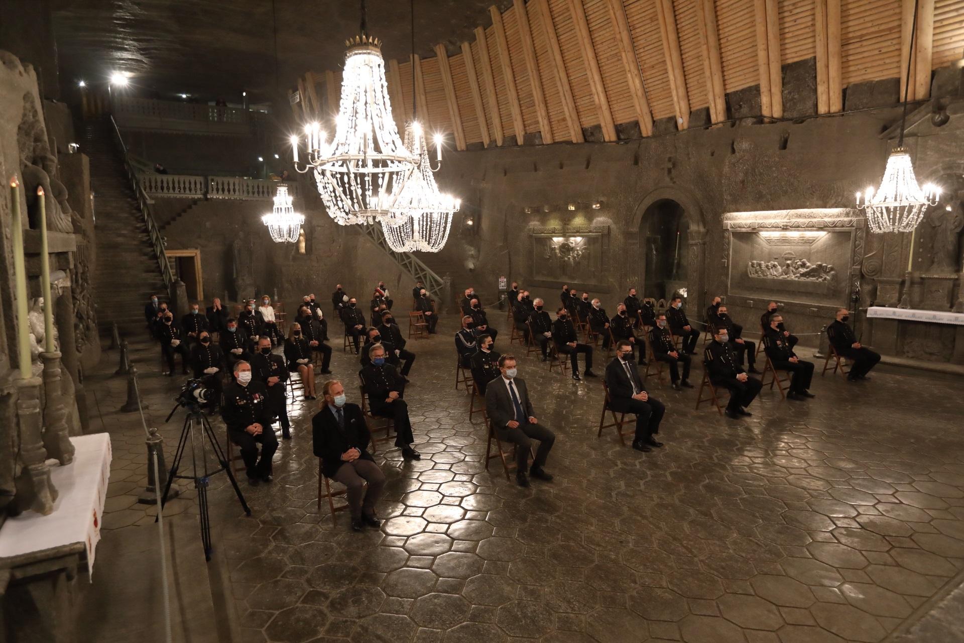 Widok na kaplicę św. Kingi. Jej wnętrze oświetlają cztery solne żyrandole. W bezpiecznych odstępach siedzą górnicy w galowych mundurach oraz zaproszeni goście