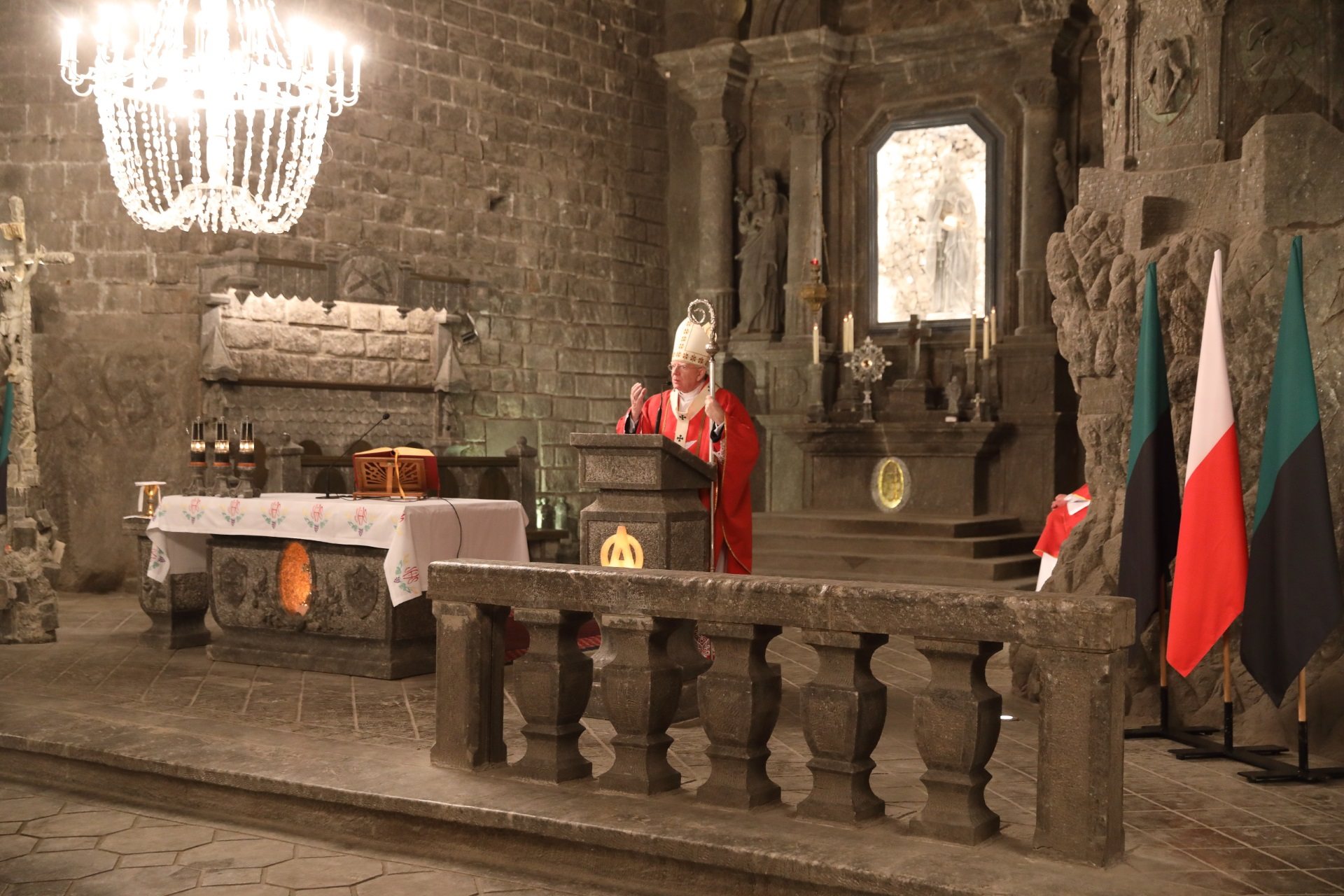 Ołtarz główny. Metropolita krakowski stoi przy solnej ambonie. W lewej dłoni dzierży pastorał. Ubrany jest w czerwony ornat