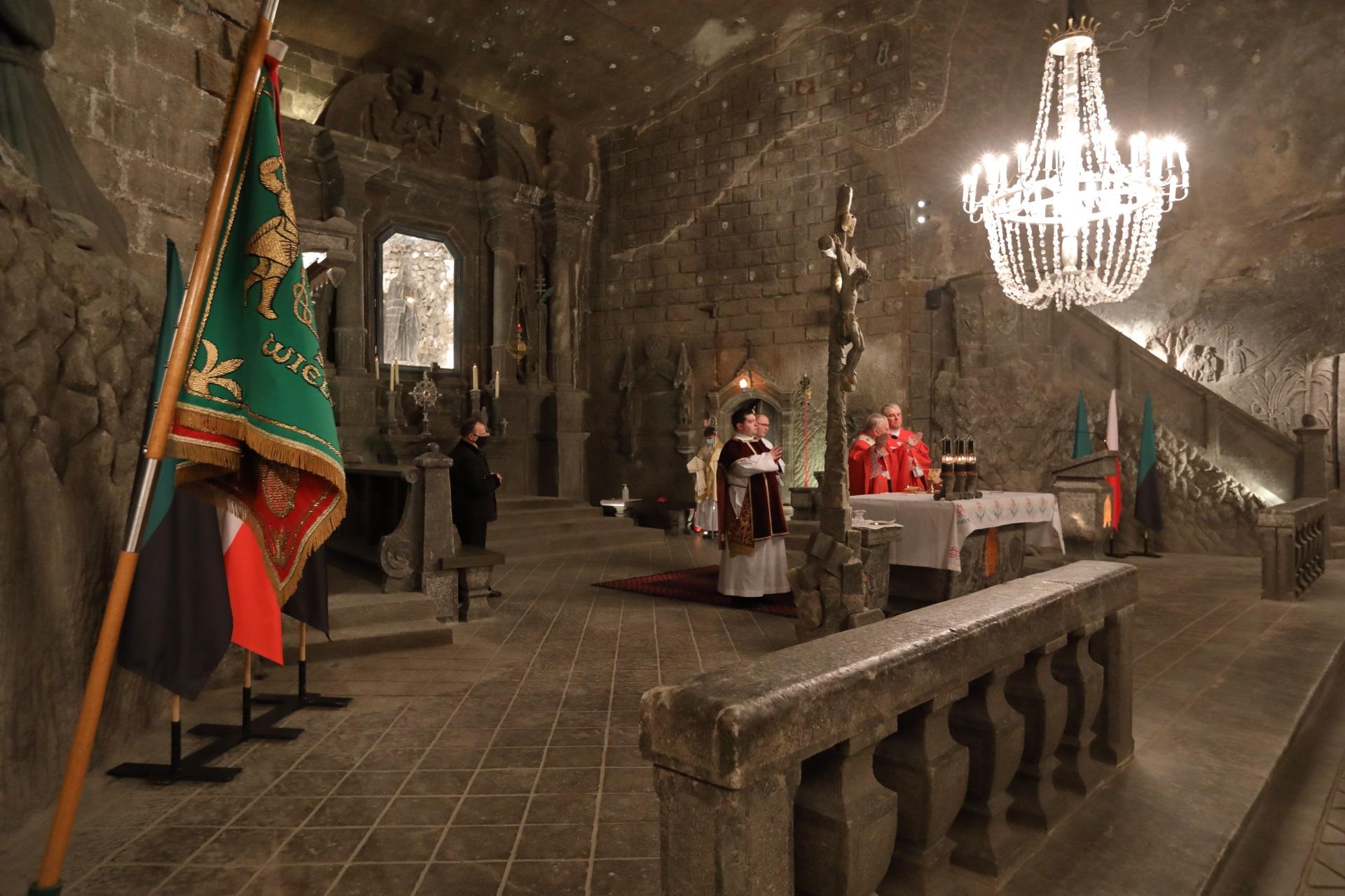 Przy stole ołtarzowym modli się arcybiskup oraz towarzyszący mu duchowni. Po lewej stronie kadry lekko pochylony górniczy sztandar. W głębi, między solną barierką a stołem ołtarzowym widoczny krzyż papieski również wyrzeźbiony w soli