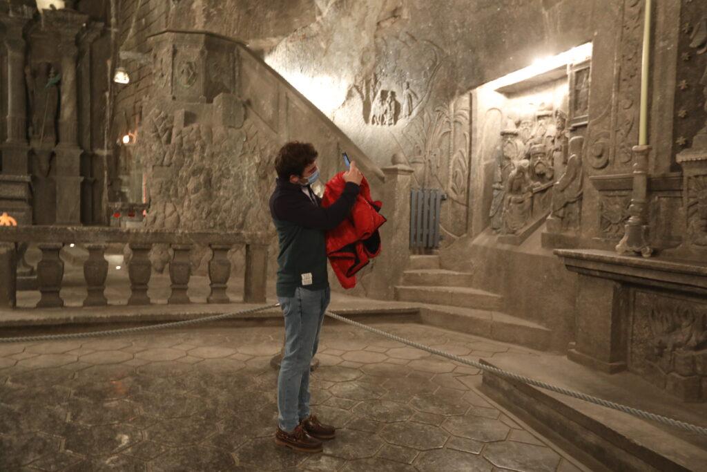 Turysta fotografuje solne detale w kaplicy św. Kingi. Mężczyzna ubrany jest w niebieskie jeansy i ciemną bluzę. Przez rękę ma przerzuconą czerwoną kurtkę. Zdjęcie robi smartfonem