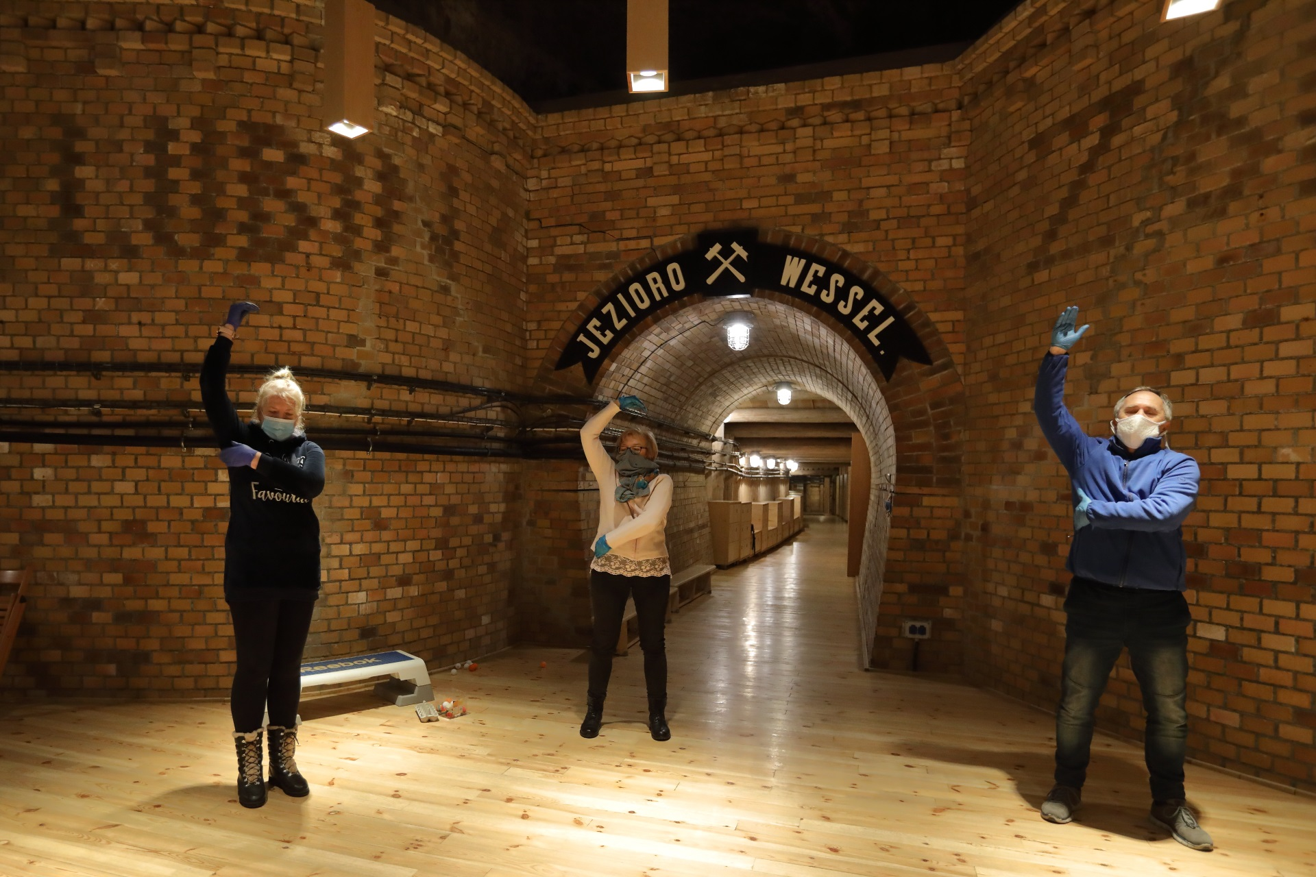 Troje kuracjuszy - dwie panie i jeden pan, wykonują ćwiczenia na tle wejścia do komory. Za nimi mur z cegły oraz napis Jezioro Wessel