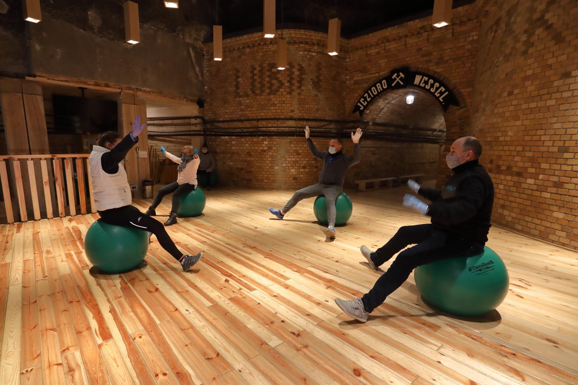 Rehabilitacja w komorze Jezioro Wessel. Troje pacjentów ćwiczy równowagę, siedząc na zielonych piłkach. Ćwiczenie demonstruje fizjoterapeutka