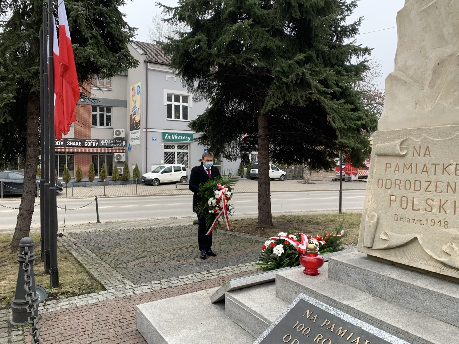 """Biało-czerwone kwiaty przed pomnikiem odrodzenia Polski składa Prezes Zarządu Kopalni Soli """"Wieliczka"""" Trasa Turystyczna Michał Roehlich"""