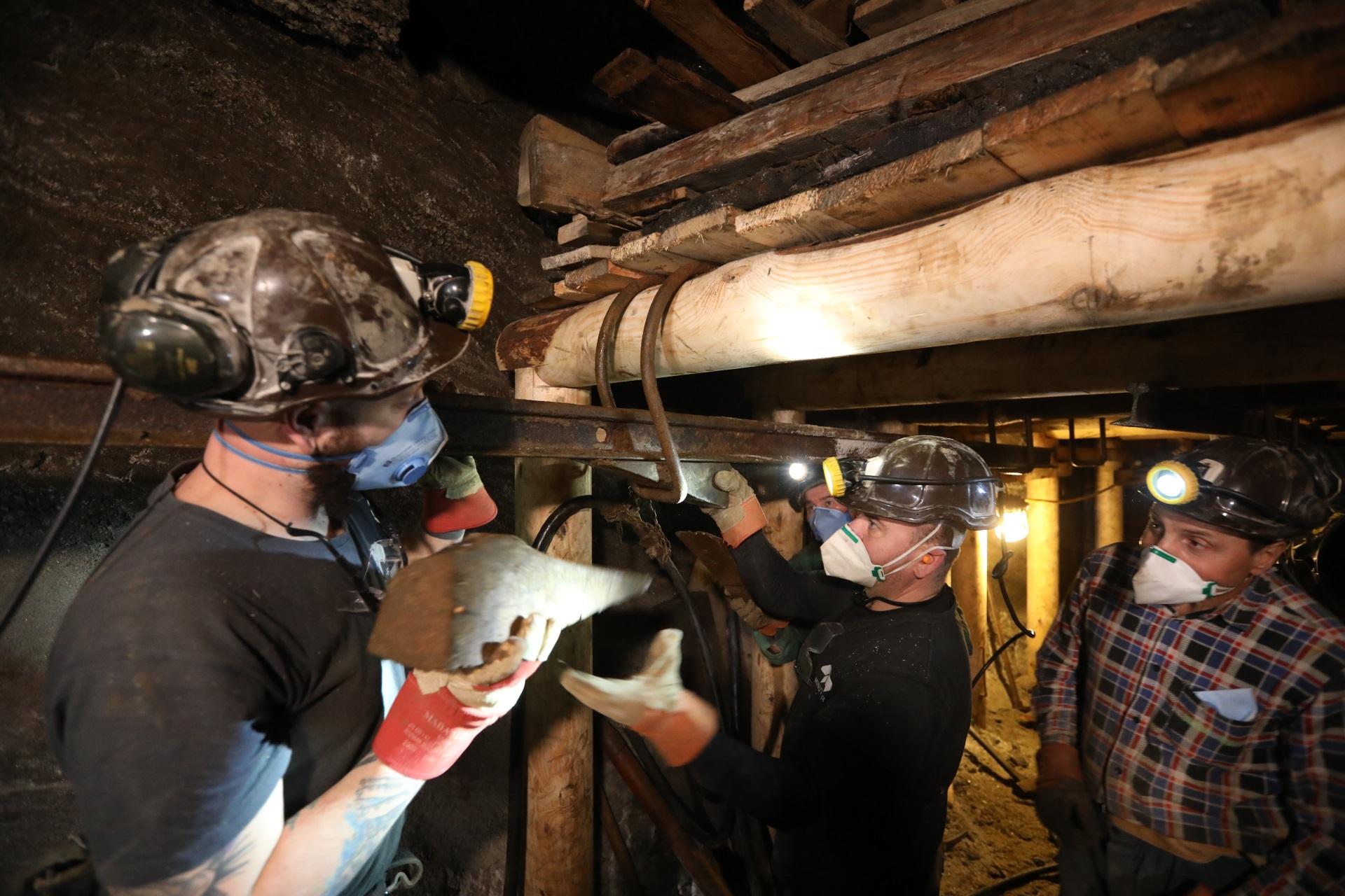 Trzech górników przy pracy w chodniku kopalnianym