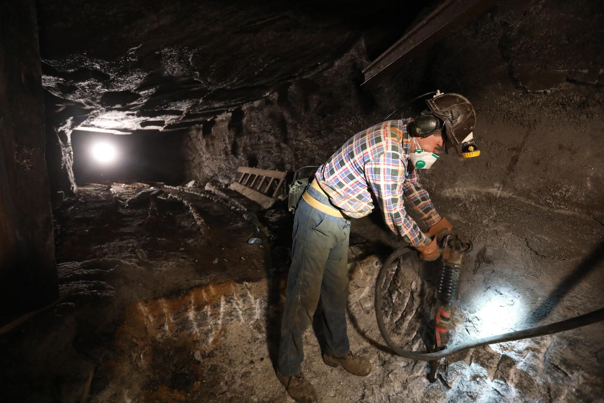 Przebudowa chodnika. Górnik w kraciastej koszuli i brązowym hełmie pracuje młotem pneumatycznym