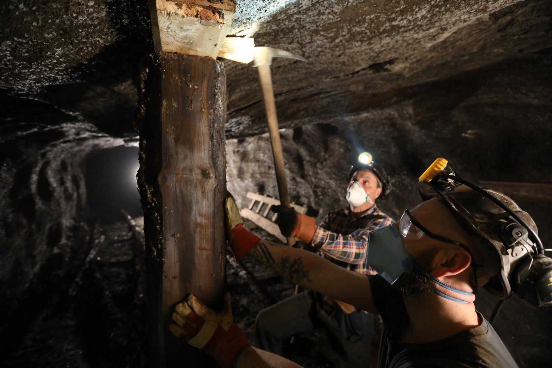 Dwóch górników klinuje drewniany stojak