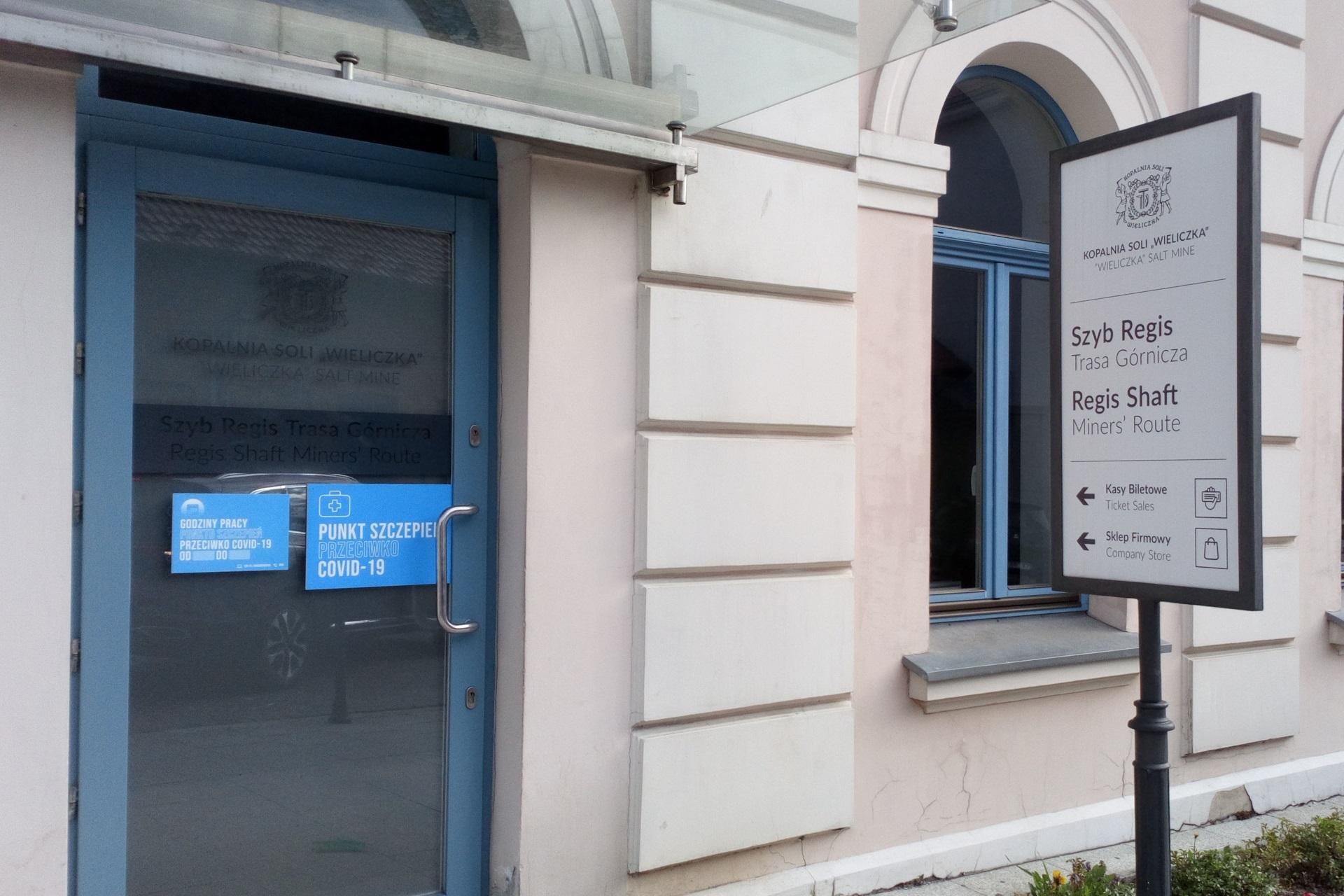 Wejście do szybu Regis. Na oszklonych drzwiach informacja na niebieskim tle: punkt szczepień