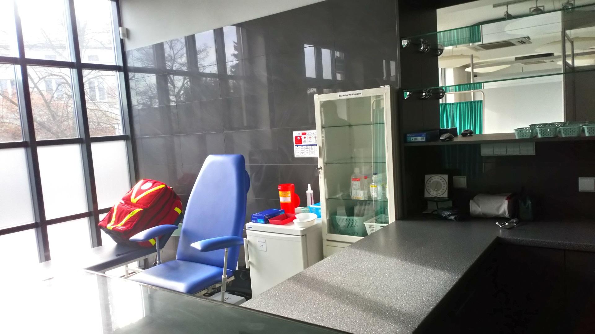 Wnętrze punktu szczepień. Niebieski fotel, oszklona szafka z medykamentami. Na leżance pod oknem czerwony plecak medyczny