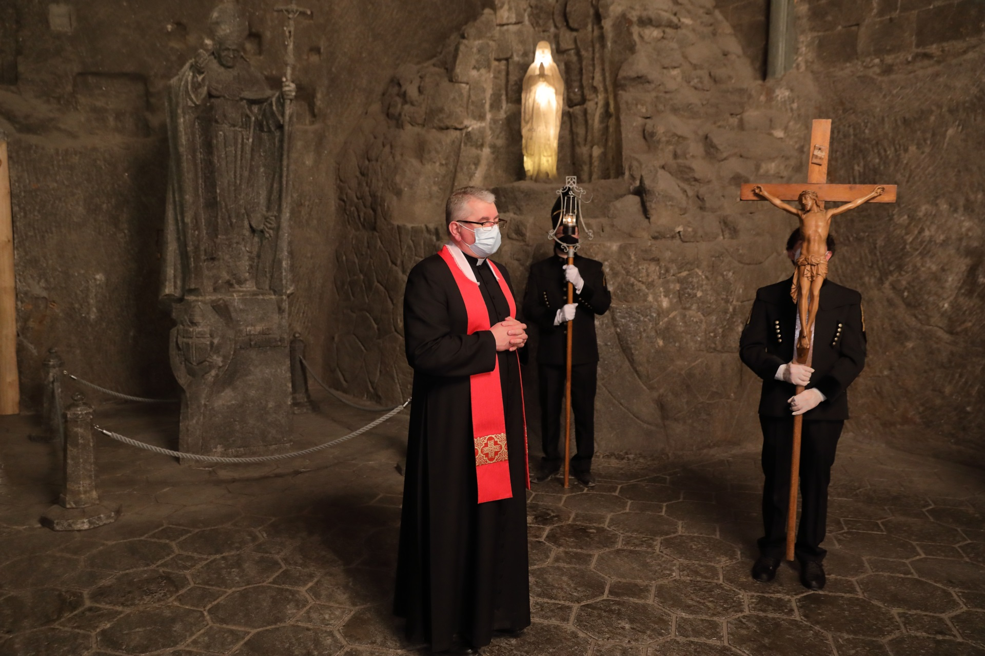 Modlitwa w kaplicy św. Kingi. Na pierwszym planie ksiądz przewodniczący nabożeństwu Drogi Krzyżowej - proboszcz parafii św. Klemensa. W tle górnicy: z krucyfiksem i zicherką. Za nimi w solnej wnęce podświetlona figurka Matki Bożej z Lourdes