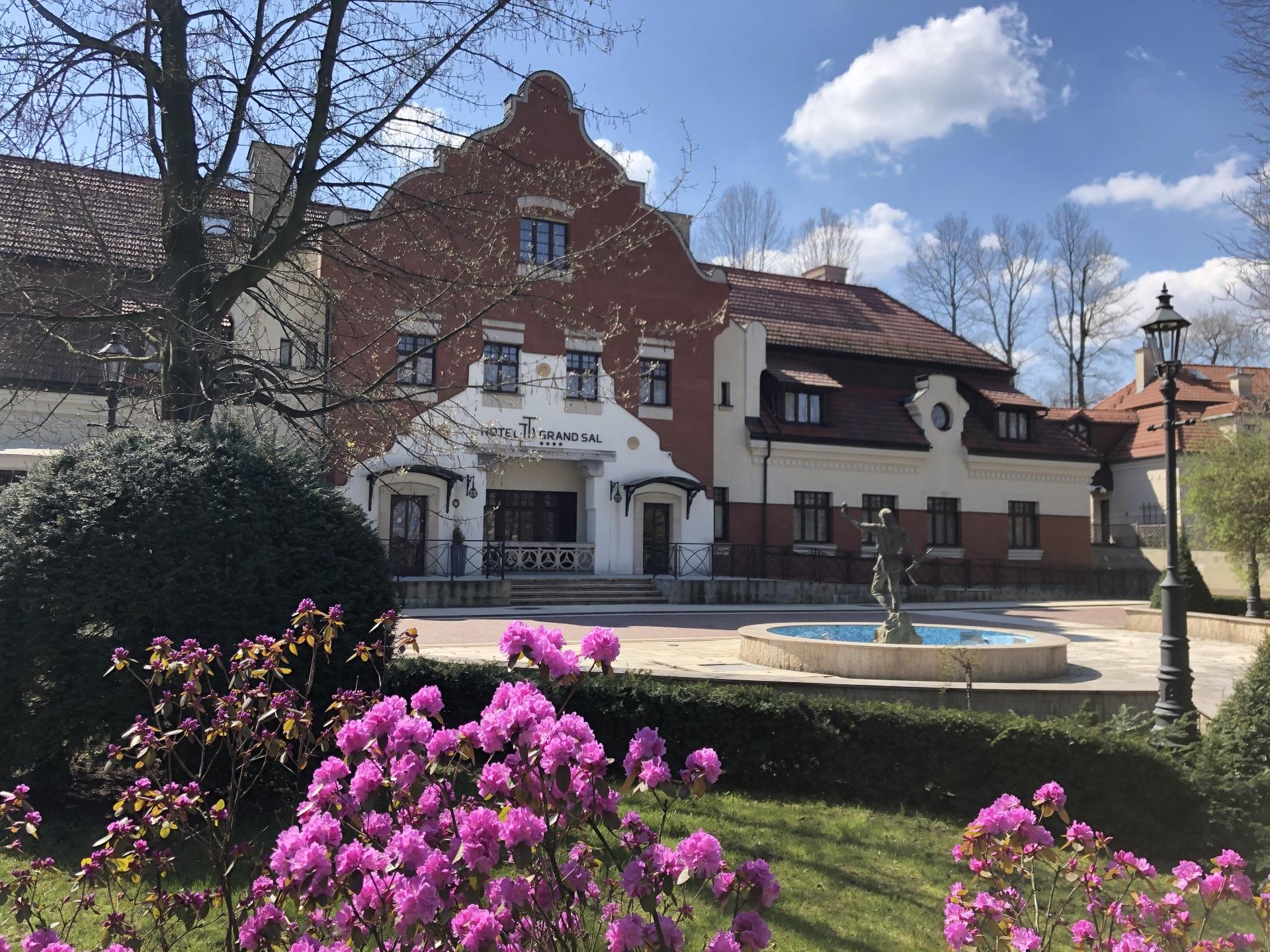 Front - Hotel Grand Sal.  Długi budynek częściowo z cegły. Za pierwszym planie kwitnące na fioletowo krzewy