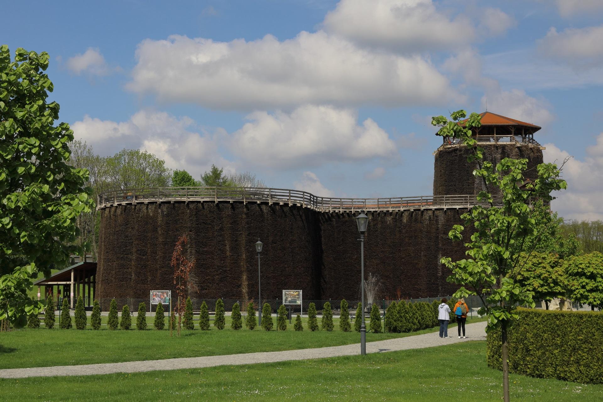 Tężnia solankowa w słoneczny wiosenny dzień. Budowla z tarniny, brązowa, z wieżą krytą pomarańczowym dachem