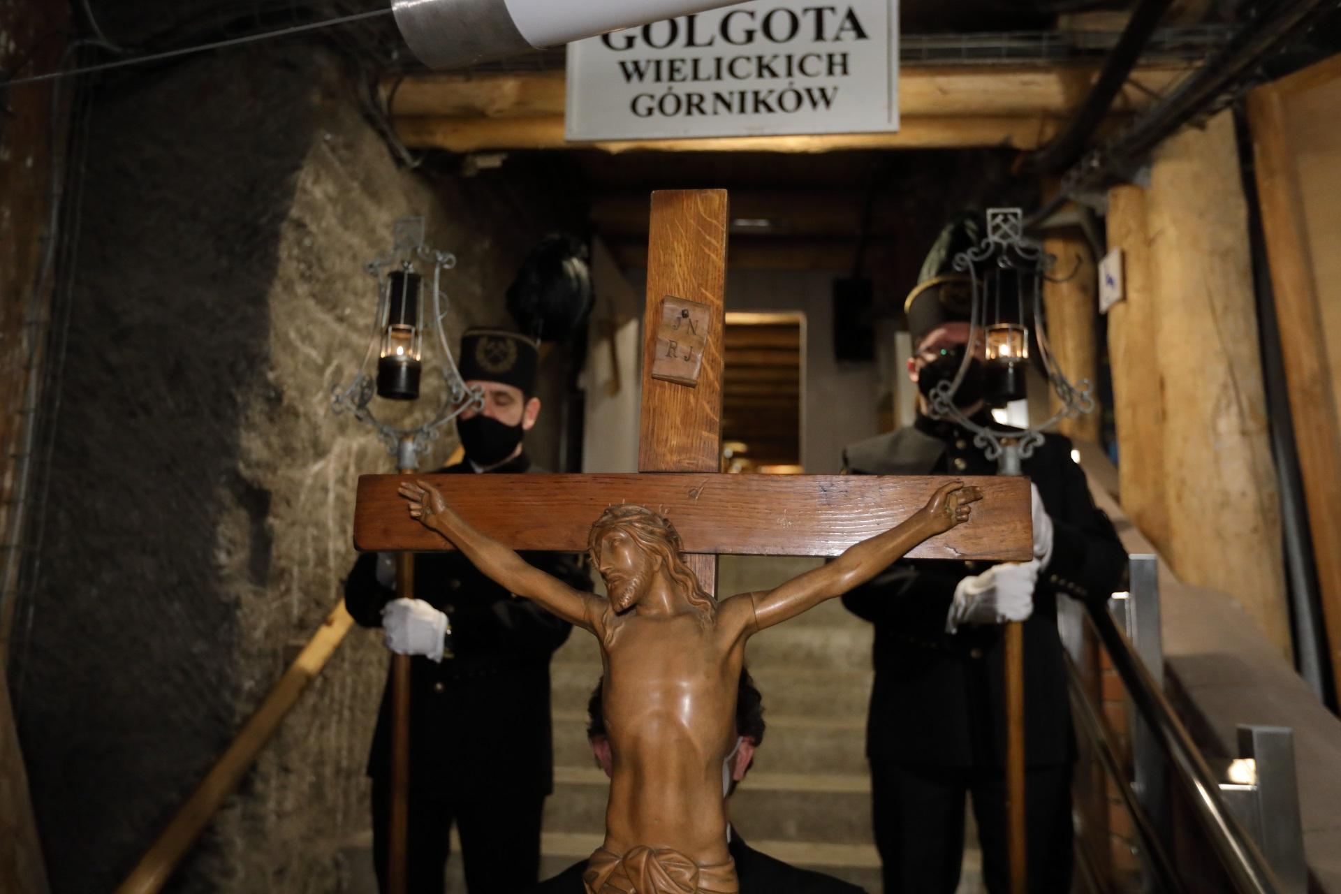 Na pierwszym planie drewniany krucyfiks. Za krzyżem stoją dwaj górnicy w galowych mundurach, z zapalonymi zicherkami. Ponad ich głowami napis na białej tablicy: Golgota wielickich górników. W tle uchylone wejście do pochylni Barącza