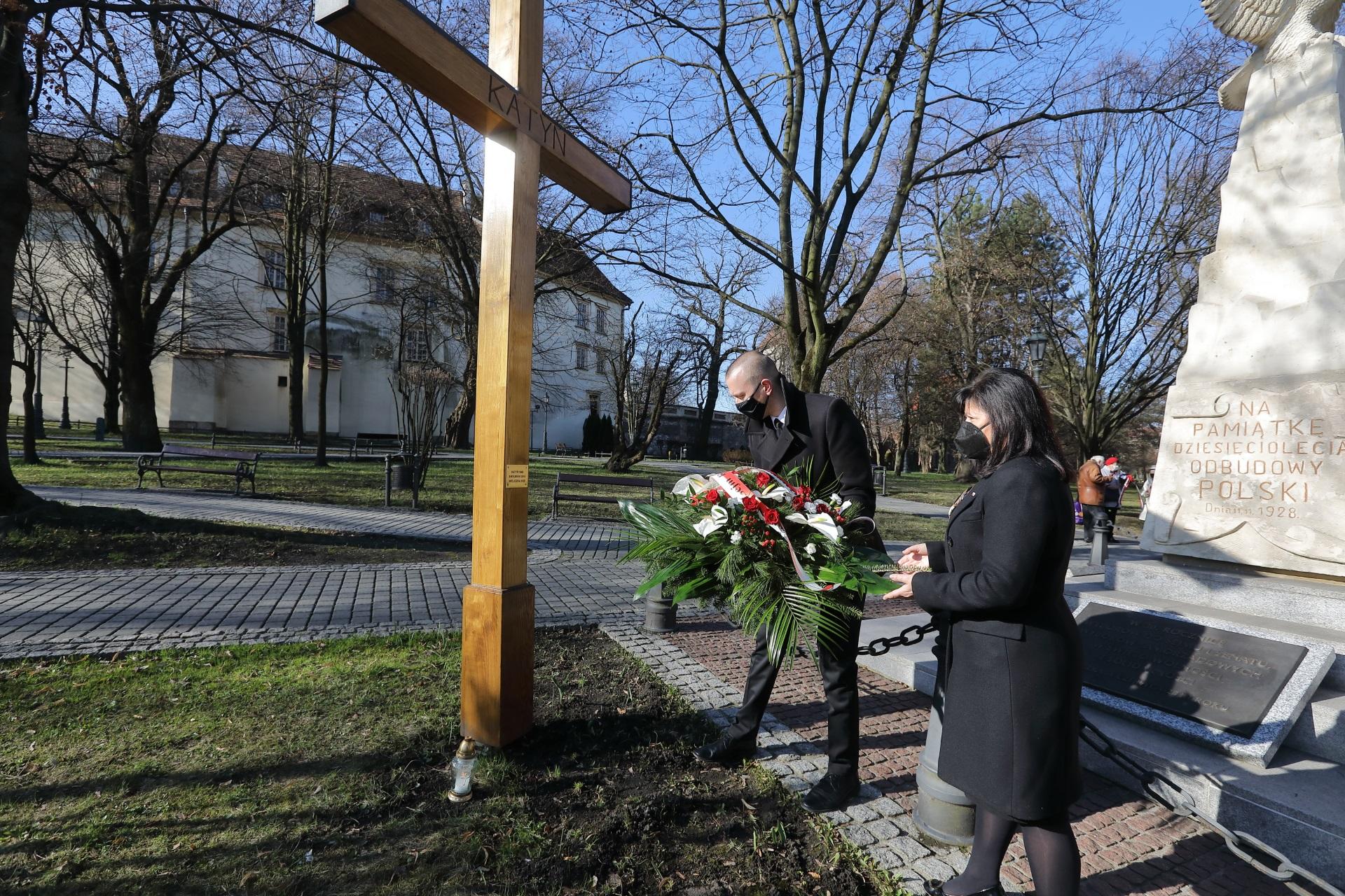 Poseł Urszula Rusecka oddaje hołd ofiarom Katynia oraz katastrofy Smoleńskiej. Asystent pani poseł kładzie biało-czerwoną wiązankę pod wysokim drewnianym krzyżem