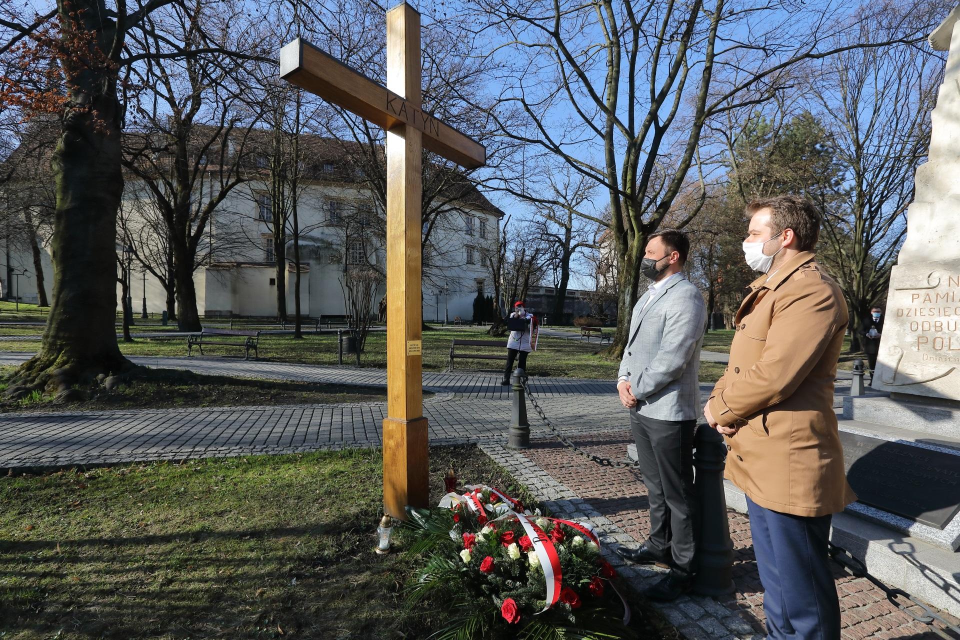 Poseł Rafał Bochenek i radny miejski Piotr Klimczyk. Spoglądają na drewniany krzyż stojący na wielickich Plantach. U stóp krzyża spoczywają biało-czerwone kwiaty