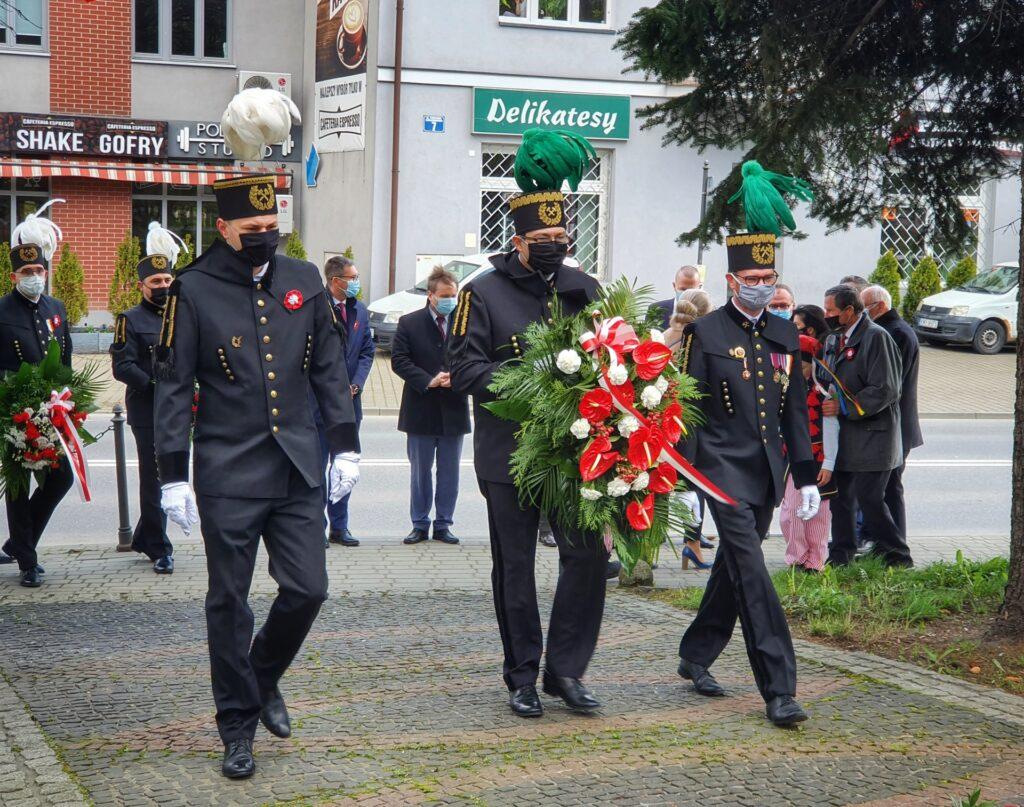 """Przedstawiciele Kopalni Soli """"Wieliczka"""" S.A. składają kwiaty w dniu 3 maja. W galowych mundurach prezes Paweł Nowak (w środku), dyrektorzy Tomasz Broniowski (po lewej) i Damian Konieczny (po prawej)"""