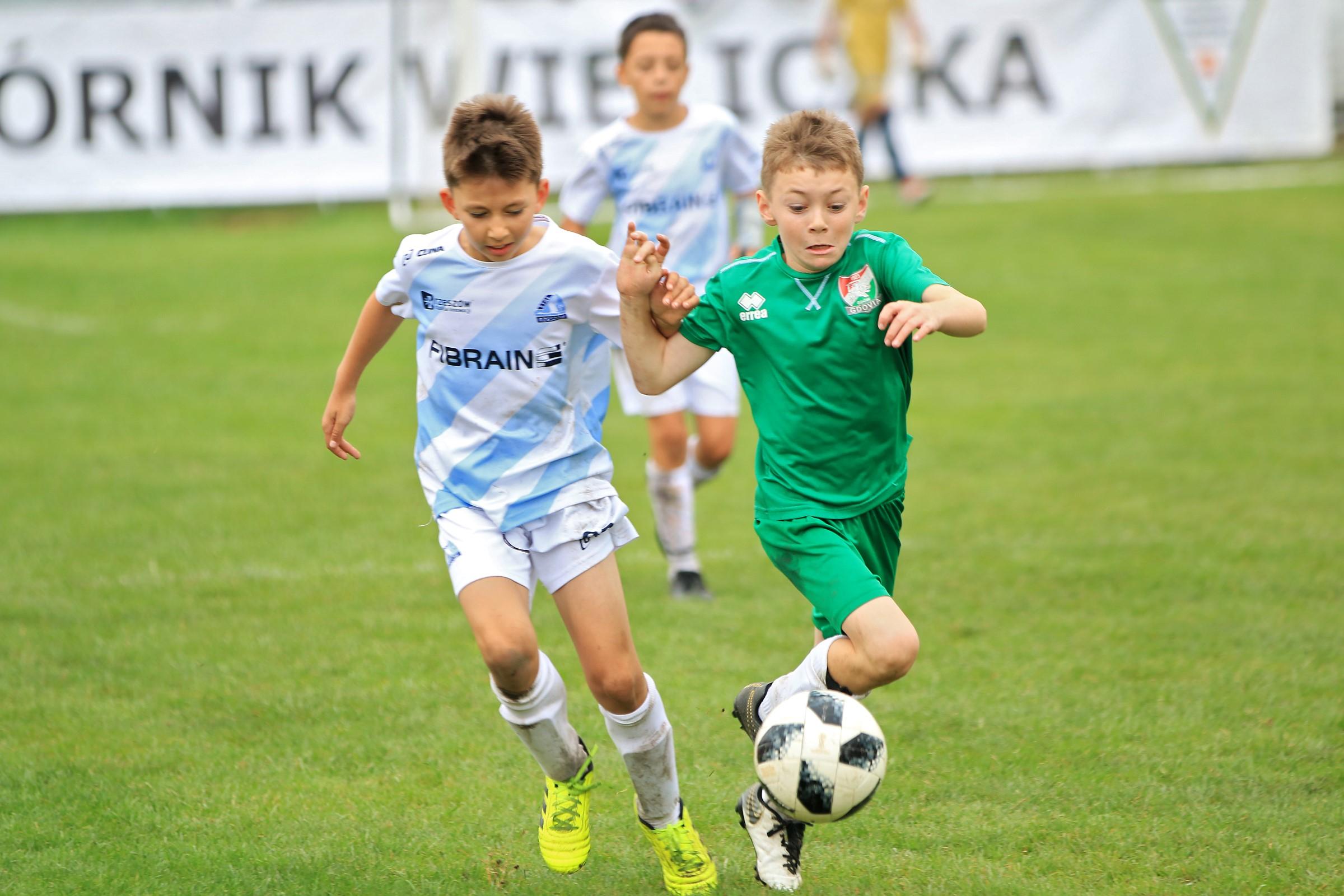 dwóch chłopców kopie piłkę
