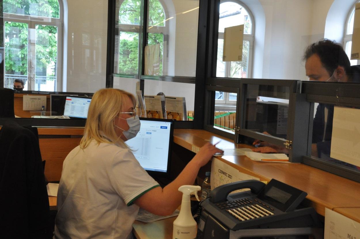 Rejestracja na szczepienie w budynku szybu Regis. Rejestratorka przyjmuje od pacjenta dokumenty