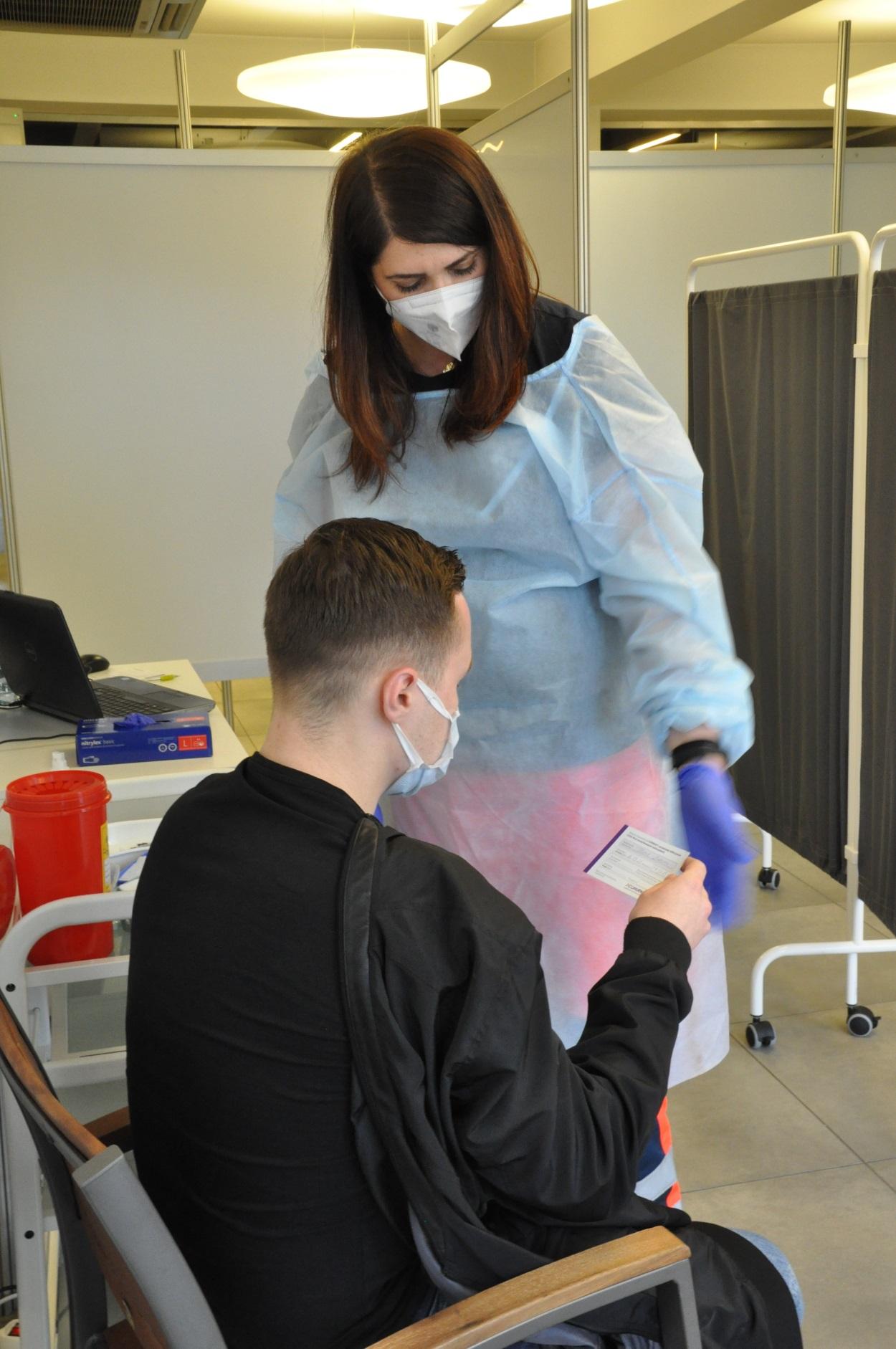 Szczepienie przeciw COVID-19. Pacjent, mężczyzna w czarnej bluzie oraz pielęgniarka wykonująca zastrzyk