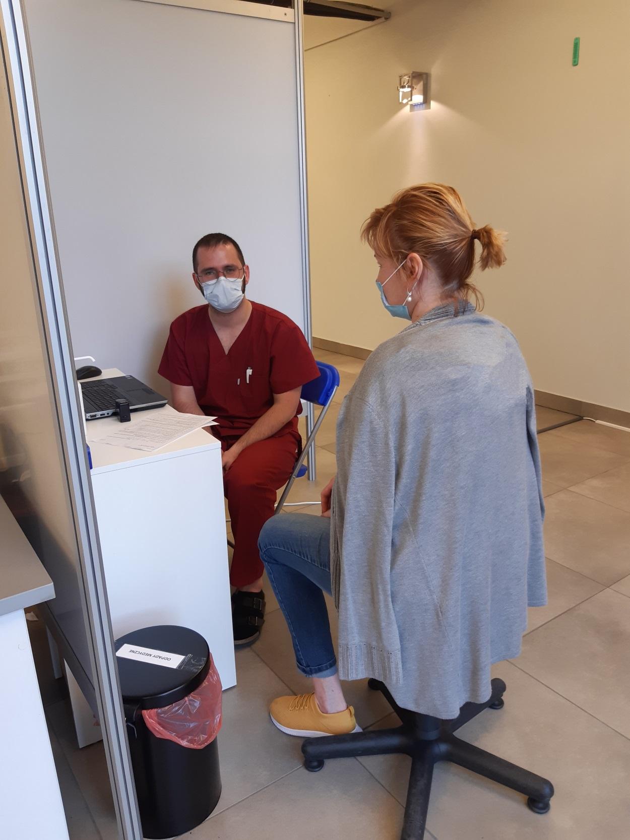 Pacjentka rozmawia z lekarzem. Kwalifikacja medyczna przed szczepieniem przeciw COVID-19