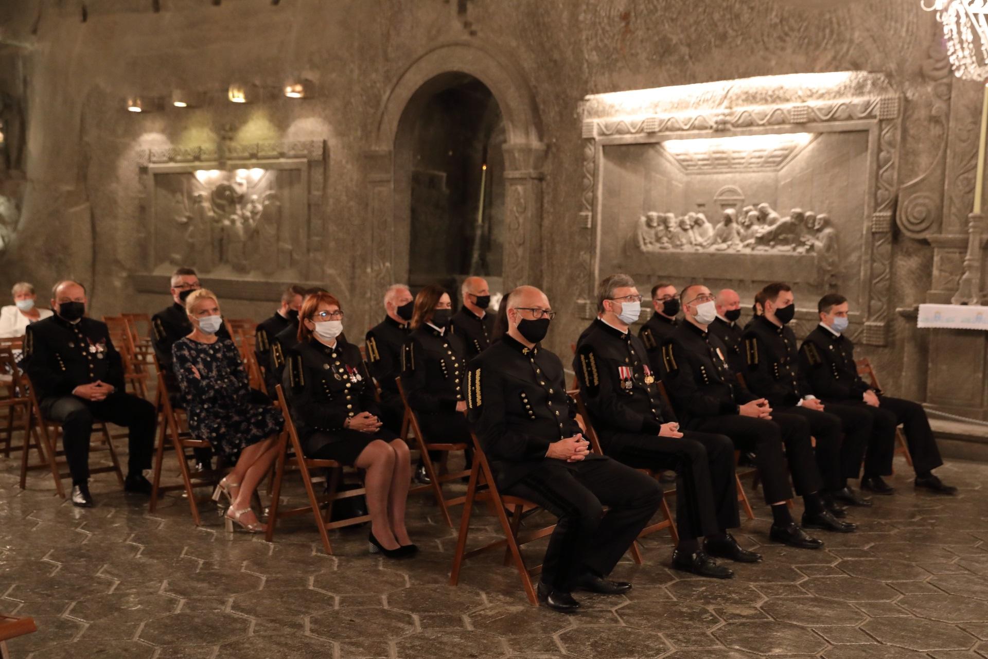 """Górnicy w galowych mundurach podczas mszy św. w kaplicy św. Kingi. W tle solna płaskorzeźba wzorowana na fresku Leonarda da Vinci """"Ostatnia Wieczerza"""""""