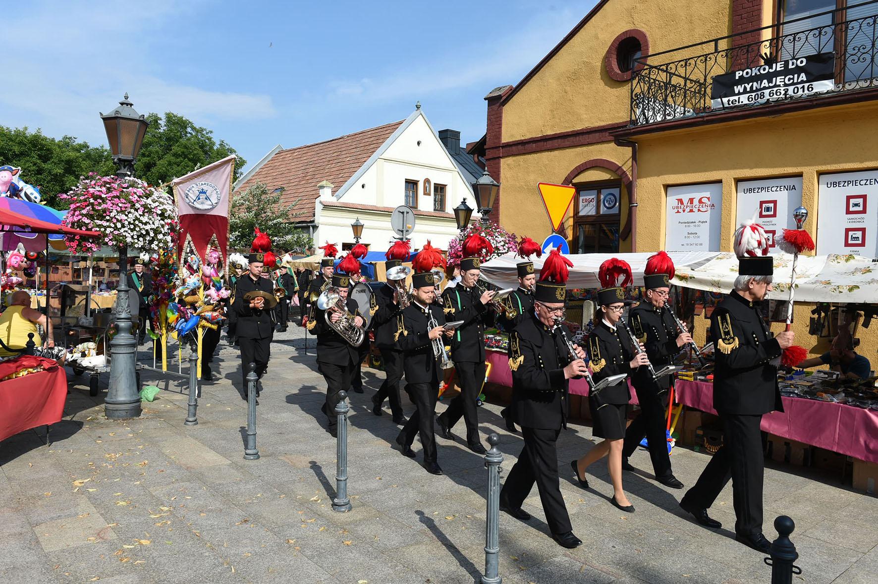 Górnicza orkiestra na uliczkach Starego Sącza. W tle tradycyjne kramy z odpustowymi słodyczami