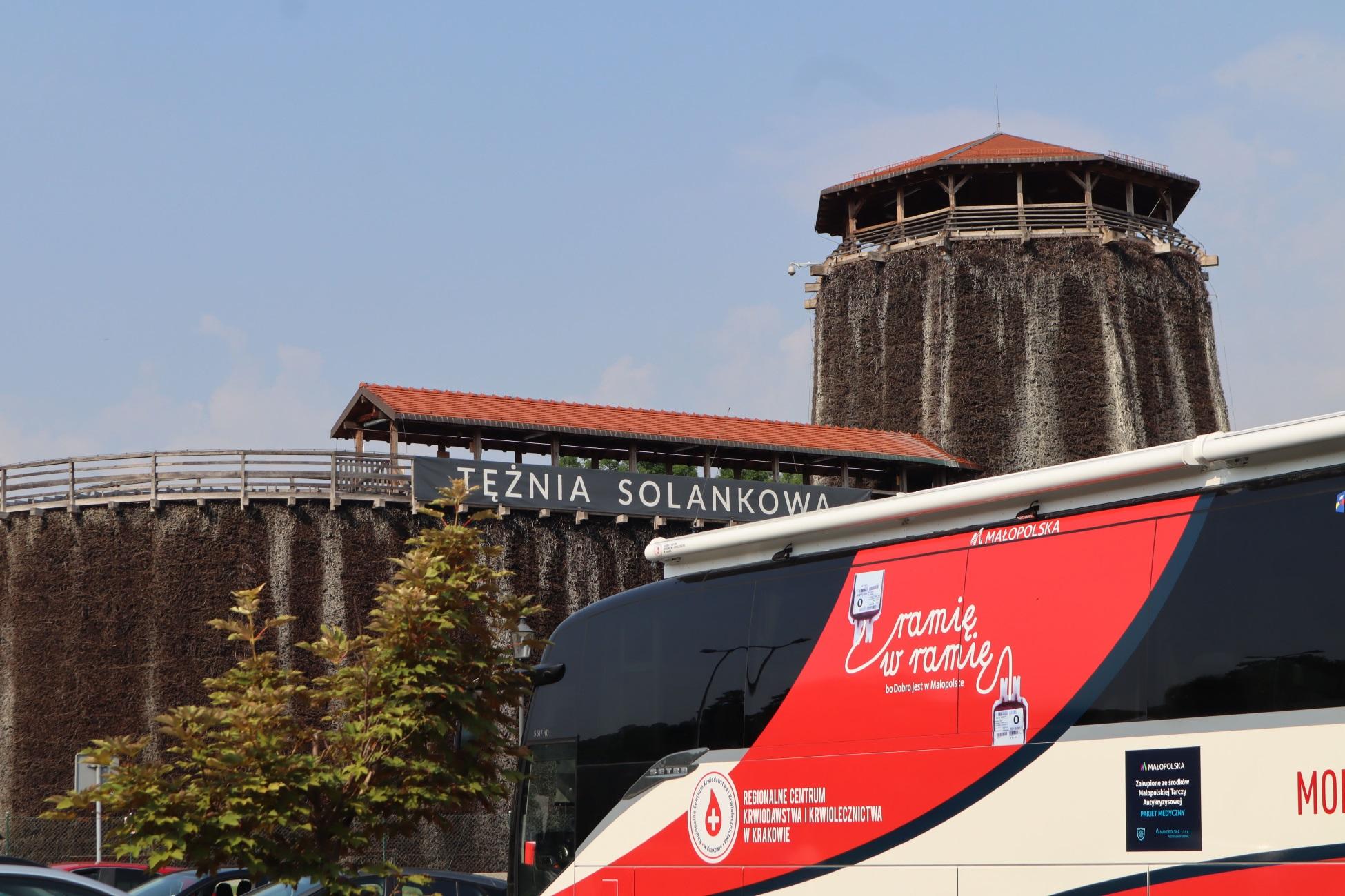 """Czerwono-biały autokar z napisem """"ramię w ramię"""". W tle tężnia solankowa - widoczny jest fragment muru oraz wieża widokowa"""