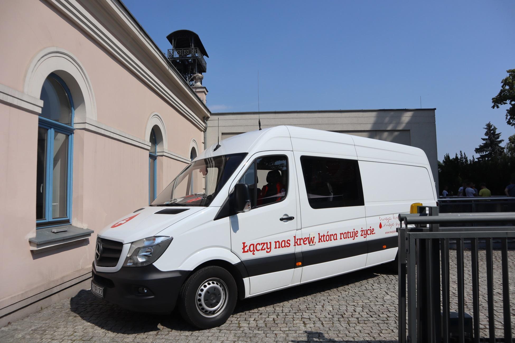 """Biały van z napisem na boku """"Łączy nas krew, która ratuje życie"""". Samochód jest zaparkowany przed budynkiem nadszybia szybu Regis"""