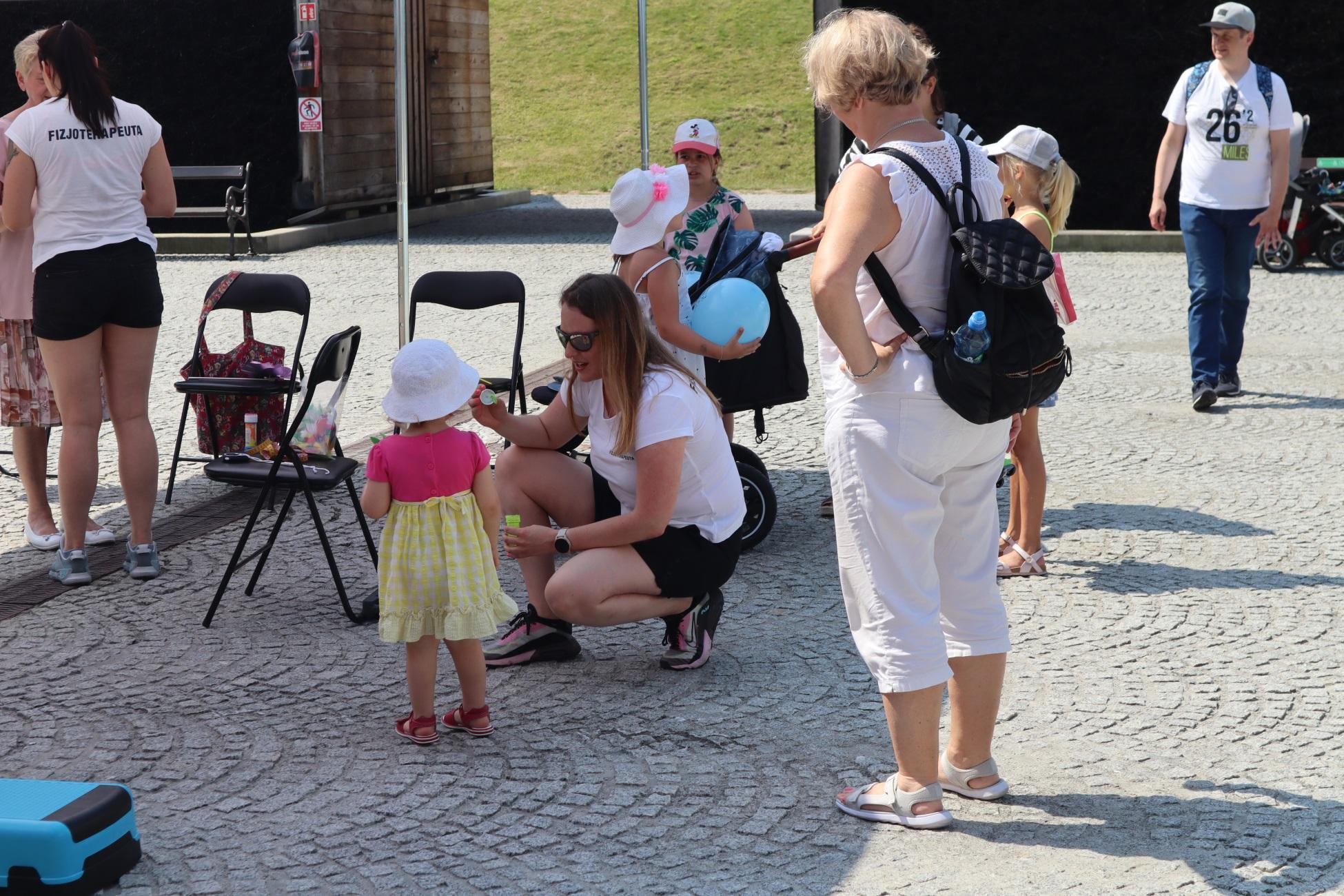 Gry i zabawy dla najmłodszych w tężni. Fizjoterapeutka kuca obok małej dziewczynki ubranej w różowo-żółtą sukienkę i biały kapelusik. Fizjoterapeutka pokazuje dziecku, jak zrobić mydlane bańki