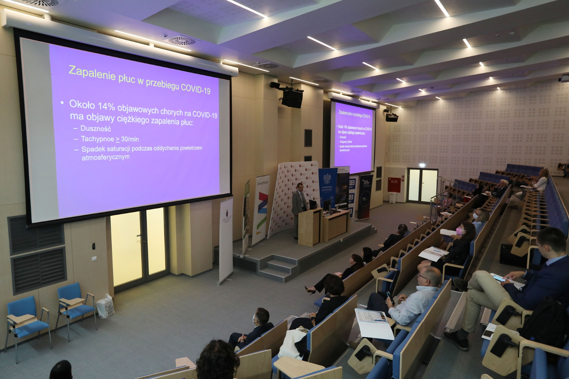 Sala konferencyjna. Na dwóch ekranach wyświetlona treść prezentacji, po prawej stronie kadru rzędy niebieskich krzeseł zajętych przez uczestników spotkania
