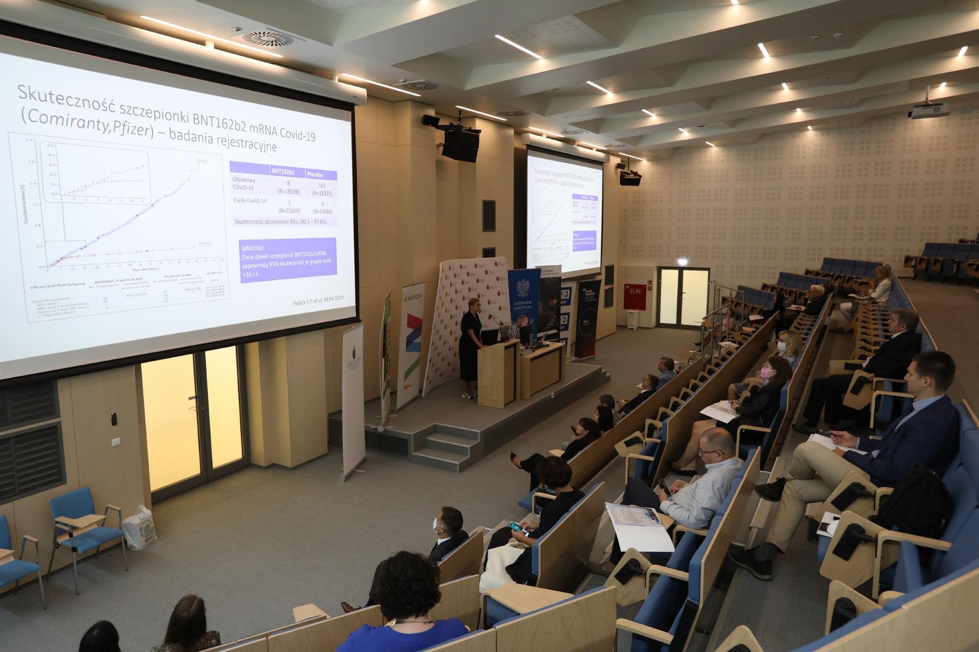 Sala konferencyjna. Na ekranie fragment prezentacji dotyczący skuteczności szczepionek przeciw COVID-19