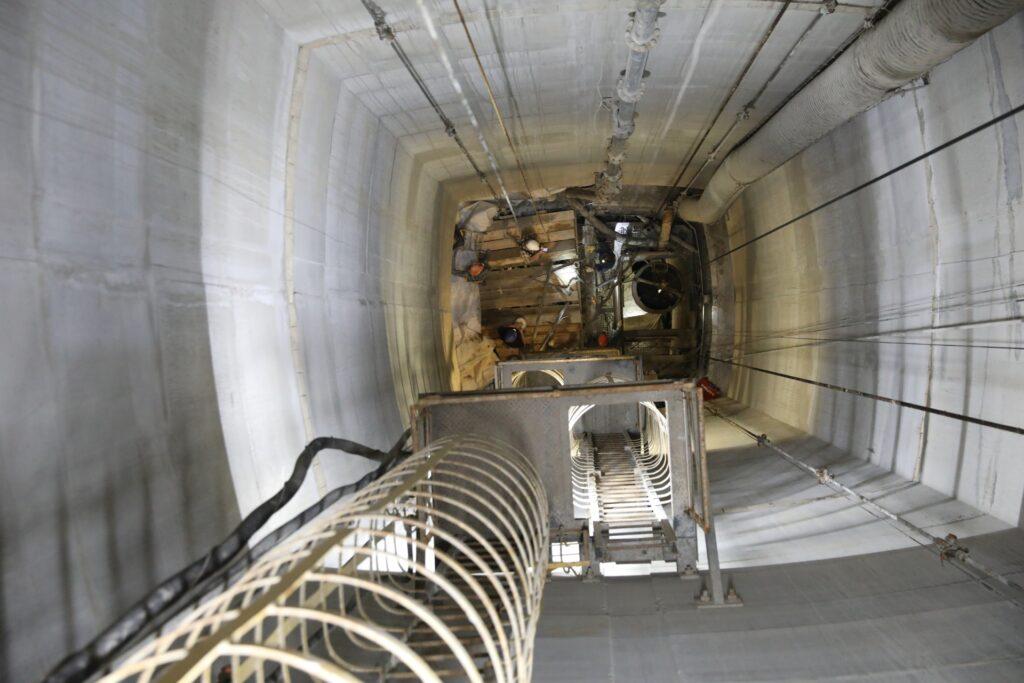 Wnętrze rury szybowej. W dole platforma, z której pracują górnicy